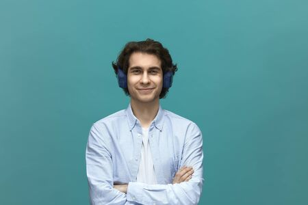 I am glad. Portrait of a young beautiful man wearing white t-shirt and blue shirt with headphones fold ones arms and looking at camera over blue background.