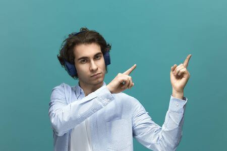 You should read this. Portrait of a young beautiful man wearing white t-shirt and blue shirt in headphones. Point to something top at right by his forefingers over blue background Archivio Fotografico