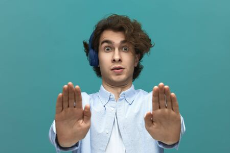 Hold on. Portrait of a young beautiful man wearing white t-shirt and blue shirt in blue headphones put forward his palms and looking at the camera over blue background