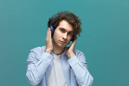 Listening sound. Portrait of a young beautiful man wearing white t-shirt and blue shirt in headphones covers ears with hands enjoying sounds over blue background
