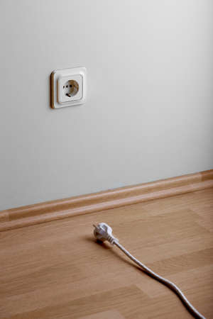 Need extension. White power socket on beige wall at low height from the floor and a short cable lies on the floor