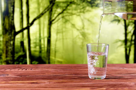 Refreshing drink water pouring with bubbles in to glass over natural green forest background