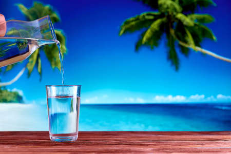 A glass full of drinking water on a wooden table over natural blue sea beach and palm trees background