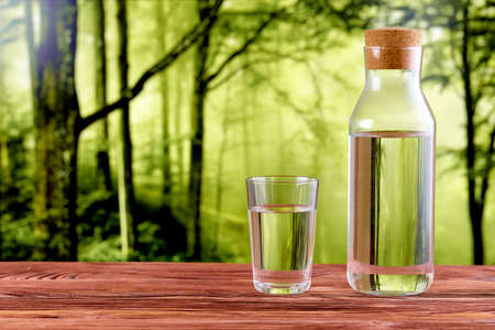 A glass and a jug full of drinking water on a wooden table over natural green forest background