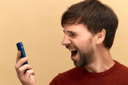 Photo of young man with beard wearing sweater screaming in anger and shock, using mobile phone, feeling frustrated about information on screen, posing against yellow background