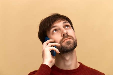 Photo of young man has phone conversation, holds mobile phone near ear, tells news to friend, focused away, wears sweater, posing against yellow background