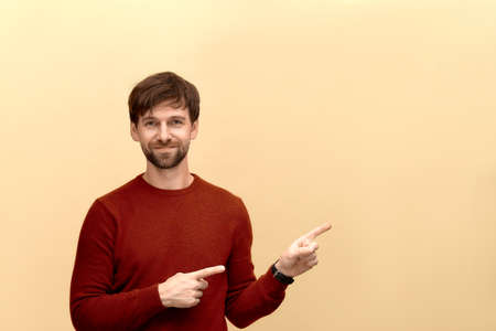 Photo of young man with beard wearing sweater, points at copy space on yellow wall as shows something pleasant, has smiling look, advertises product.