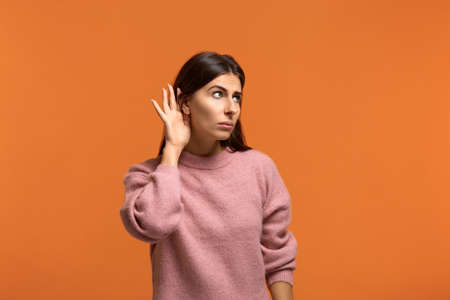 I want to hear everything. I want to know. Curious woman in pink sweater holds and near ear and to overhear interesting information against orange background indoor