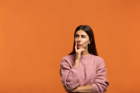 What are they doing. why. Pensive woman in pink sweater, holds finger and near mouth, looks aside and contemplates about something over orange background indoor