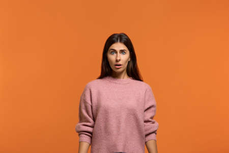 Can not be. Stupefied attractive woman in pink sweater looks with astonishment into camera, being amazed with news. Expresses surprises, doesn't believe his eyes. isolated on orange background 版權商用圖片