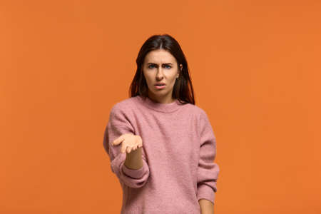 Why did you do that. Portrait of Indignant shocked beautiful woman in pink sweater keeps palm raised, cant understand something, isolated on orange wall