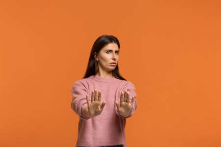 It s not for me. Portrait of woman in pink sweater, shows refusal gesture has dissatisfied facial expression as sees something abominable or detestable, isolated on orange background