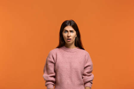 Are you serious. Portrait of shocked stunned beautiful woman in pink sweater, looking dissatisfied and surprised. Isolated on orange background