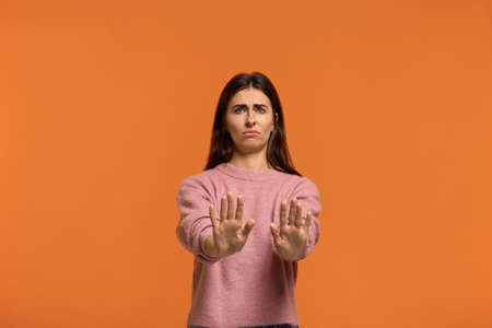 ugh what disgusting. Portrait of woman in pink sweater, shows refusal gesture has dissatisfied facial expression as sees something abominable or detestable, isolated on orange background