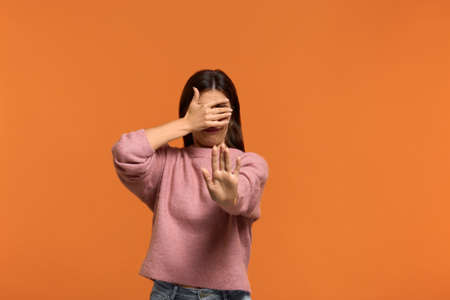 Dont show me this. Portrait of woman in pink sweater, makes denial hand gesture, demonstrates stop sign by palm, and covers eyes with palm says no to somebody. isolated on orange wall
