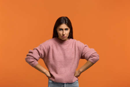 I'm very angry. Portrait of serious woman in pink sweater, holding hands on hip, frowning, having grumpy angry look, dissatisfied with something. isolated on orange wall