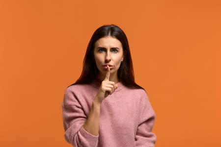 I demand complete silence. Serious beautiful woman in pink sweater with mysterious look, keeps index finger over lips, makes hush sign, looks at camera. isolated on orange background Stok Fotoğraf