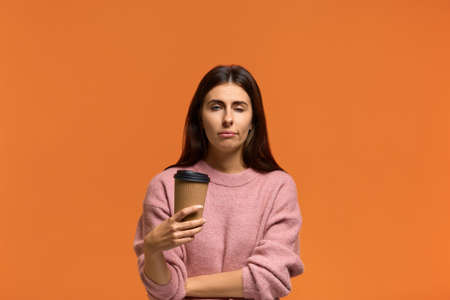Its morning already. Displeased sleepy overworked woman in pink sweater closes eyes from weariness, holding takeaway drink, feels fatigue after learning or working. isolated on orange background