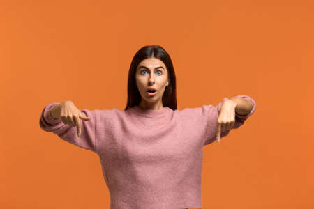 Astonishingly. Photo of attractive joyful female with dark hair, points down, has happy expression. amazed what she saw. wears in pink knitted sweater isolated over orange background