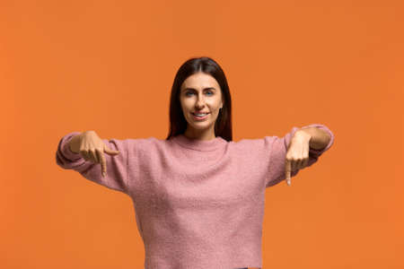Wow, just look at this offer. Photo of attractive joyful female with dark hair, points down, has happy expression. glad to be lucky. wears in pink knitted sweater isolated over orange background