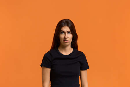ugh, don't eat it. Angry dissatisfied caucasian woman in black t-shirt disgusting expression as sees something unpleasant, frowns face raised eyebrow. Female isolated over an orange background. Archivio Fotografico