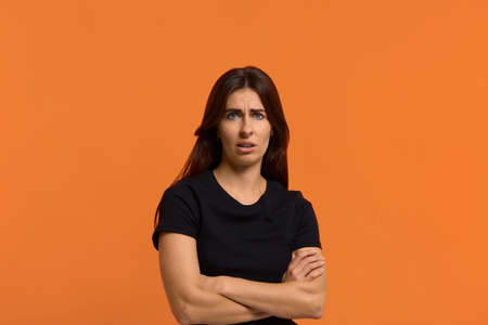 Dissatisfied caucasian woman in black t-shirt disgusting expression as sees something unpleasant, keeping arms crossed and open mouth. Female isolated over an orange background Archivio Fotografico