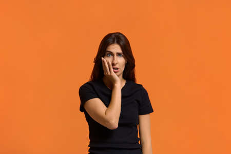 Shocked caucasian woman in black t-shirt disgusting expression as sees something unpleasant, keeping palm on her cheek. Female isolated over an orange background. Archivio Fotografico
