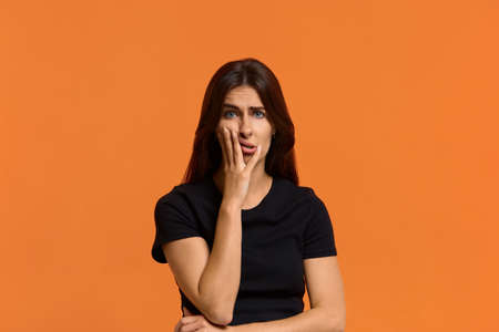 Shocked caucasian woman in black t-shirt disgusting expression as sees something unpleasant, keeping palm on her cheek, makes a grimace. Female isolated over an orange background Archivio Fotografico