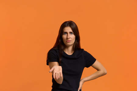 Dissatisfied caucasian woman in black t-shirt disgusting expression as sees something unpleasant, keeping palm up the other hand on the belt. Female isolated over an orange wall Archivio Fotografico