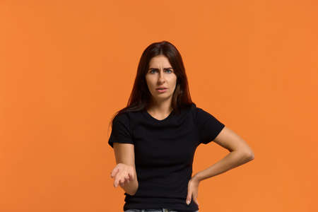 what are you talking about. Dissatisfied caucasian woman in black t-shirt disgusting expression as sees something unpleasant, keeping palm up, ask question. Female isolated over an orange background