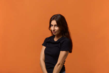 Charming caucasian woman in black t-shirt, looks shy and obedient, has innocent expression, looks gladfully at camera, waiting for the first step from a guy. Isolated over an orange background