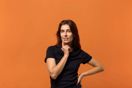 What will he present. Pleasant caucasian woman in black t-shirt keeps fore finger near lips, being deep in thoughts, thinks about something good. Dreaming about present. Isolated over an orange wall.