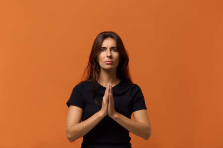 Confident caucasian woman in black t-shirt practicing yoga, holding hands in namaste, praying for peace and love, having calm and peaceful facial expression. Isolated over an orange background