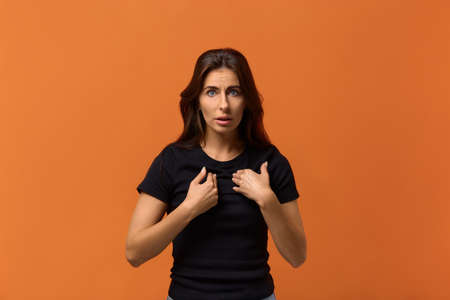 Shocked confused caucasian woman in black t-shirt points or indicates at herself with hands, surprised be accused of fault or thing she did not do, proves rightness. Isolated over an orange background