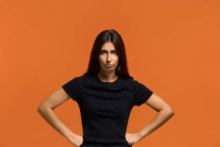 I am very angry. Portrait of serious caucasian woman in black t-shirt, holding hands on hip, frowning, having grumpy angry look, dissatisfied with something. Isolated over an orange background