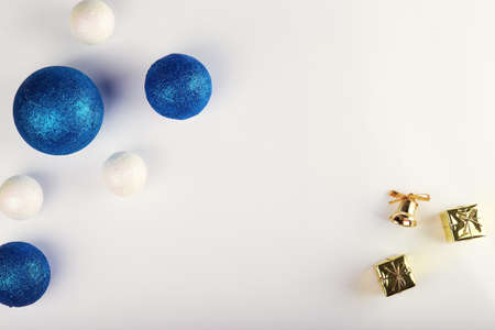 Horizontal shot of blue balls and decorative snowballs at left. With gold presents at right. on white background. Top view with copy space for text Standard-Bild