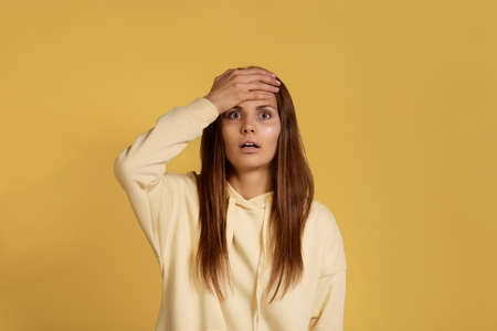 I forgot about important task. Surprised troublesome caucasian woman in yellow hoodie keeps palm on forehead, regrets did something wrong, face problematic situation. Isolated on a yellow background