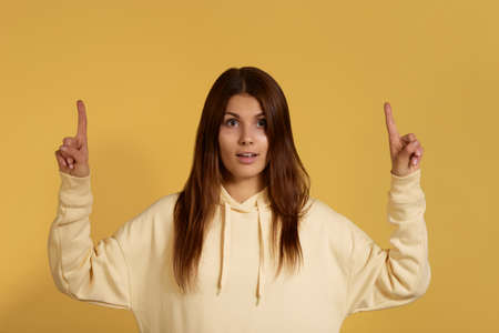 Good looking caucasian female in yellow hoodie with tanned skin looks in amazement, points upwards, pretty young woman sees amazing thing up, suggests click banner, isolated on yellow background
