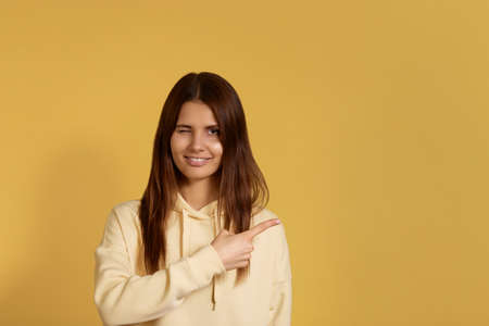 Young pretty smiling caucasian woman in a yellow hoodie blinks with eyes, indicates right, explains simple topic in comic way, introduces new product, conducts webinar, isolated on yellow background