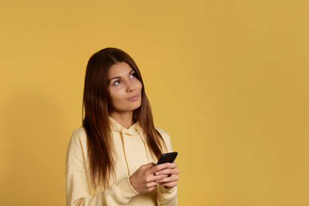 Dreamy beautiful caucasian woman in yellow hoodie looks upwards, holds mobile phone in hands, imagines a meeting, texts message, uses app, enjoys online communication, isolated on yellow background