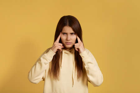 I need painkiller. Stressful caucasian woman in yellow hoodie keeps fingers on temples, suffers from headache, suffering from migraine, feels tired. Isolated on a yellow background