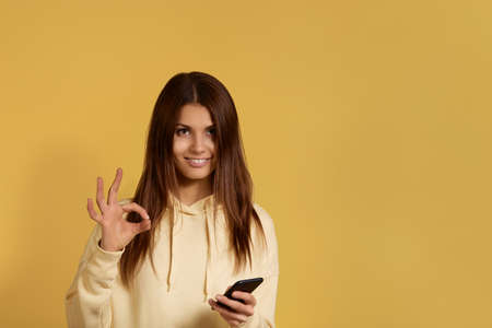 Smiling pretty caucasian woman in yellow hoodie makes okay gesture, holds mobile phone in hand, likes good conversation, gives her approval, isolated on yellow background, blank space on right side