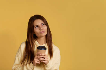 Pensive beautiful european woman in yellow hoodie holds takeout coffee, pouts lips, looks aside, dreams about something pleasant, isolated on yellow background, blank copy space on right side