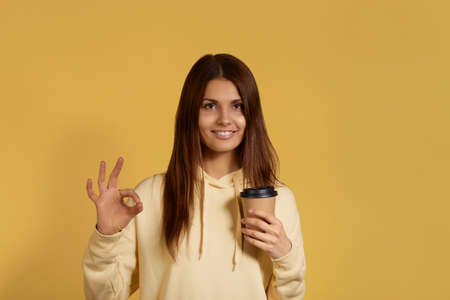 Smiling pretty caucasian woman in yellow hoodie makes okay gesture, holds takeout coffee in hand, likes takeaway drink, has excellent mood, confirms information, isolated on yellow background