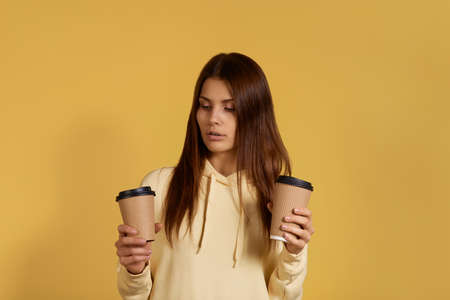 Pensive beautiful caucasian woman in yellow hoodie holds two cups of takeout coffee in hands, is in doubt which takeaway drink to choose, opens mouth, isolated on yellow background