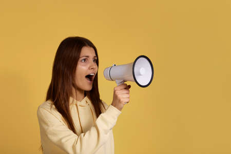 Pretty young caucasian brunette woman in yellow hoodie is screaming, shouting in megaphone, speaks loud, breaks silence, idea for marketing or sales, attracts attention, isolated on yellow background