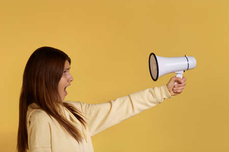 Crazy dark-haired young caucasian woman in yellow hoodie shouting at megaphone turned to her, screaming at loudspeaker, replies loudly, disagrees, shows protest, isolated on yellow background