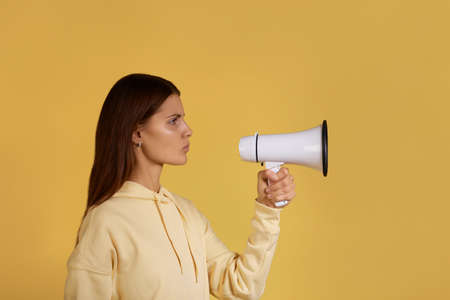 Protest. Young calm caucasian woman in yellow hoodie stands quiet holding a megaphone, ready to speak out at loudspeaker, disagrees, shows her opinion, isolated on yellow background
