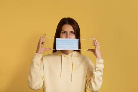 Indifferent calm young caucasian female in yellow hoodie holds medical mask in front of her, demonstrates how to put it on, comes to see doctor, has virus infection, isolated on yellow background