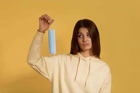 Suspecting unpleased young caucasian woman in yellow hoodie holds medical mask in hand, unwilling to put it on, doubts, comes to see doctor, has virus infection, isolated on yellow background